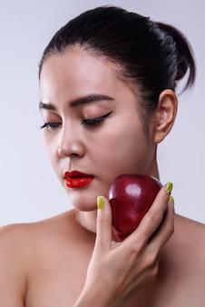 Mulher asiática com maçã vermelha na mão, conceito de saúde