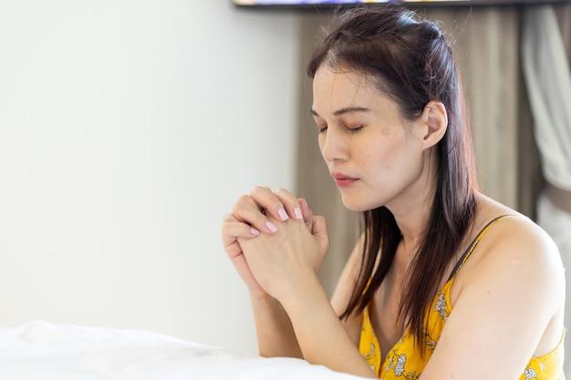 Mulher asiática com mão orando, mãos postas em oração na cama. conceito de fé, espiritualidade e religião.