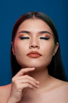 Mulher asiática com maquiagem completa e ombros nus, posando com os olhos fechados e o dedo no queixo