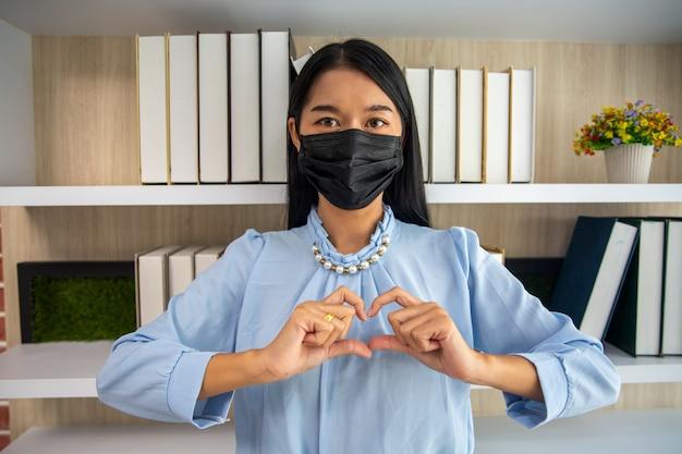 Mulher asiática com máscara facial de cor preta fazendo formato de coração para a câmera