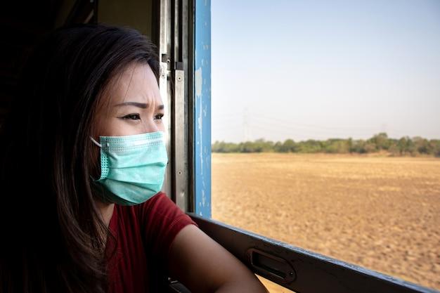 Mulher asiática com máscara facial e olhando pela janela do trem