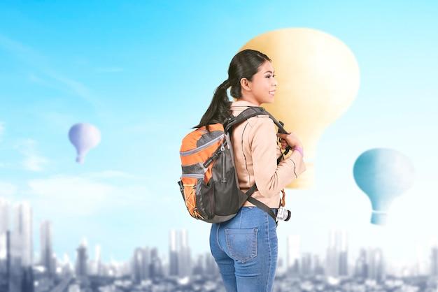 Mulher asiática com mochila olhando para um balão de ar colorido voando com o fundo da cidade