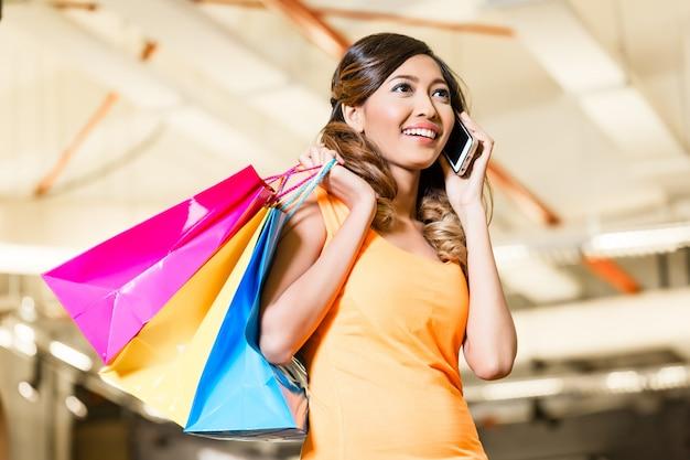 Mulher asiática com moda de compras de telefone