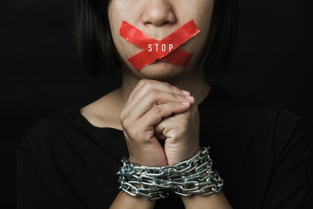 Mulher asiática com os olhos vendados envolvendo a boca com fita adesiva vermelha e ela foi amarrada à mão