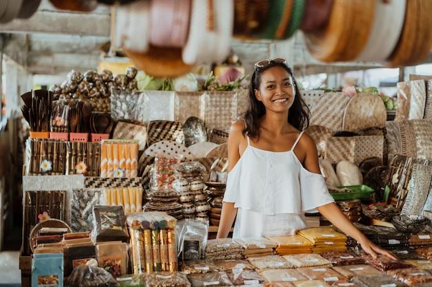 Mulher asiática com pele bronzeada na loja de souvenirs