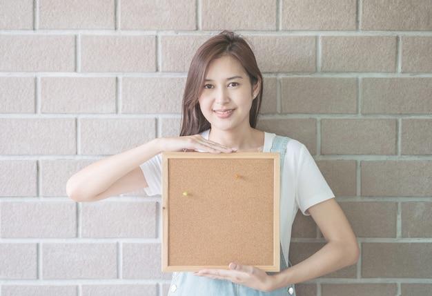 Mulher asiática com placa de cortiça na mão com cara sorridente