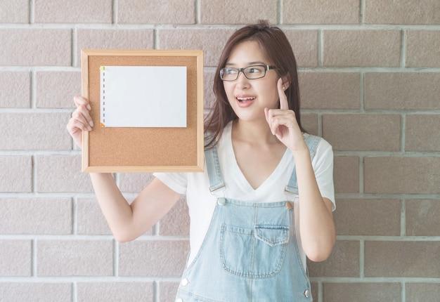 Mulher asiática com placa de cortiça na mão com ter uma cara de idéia