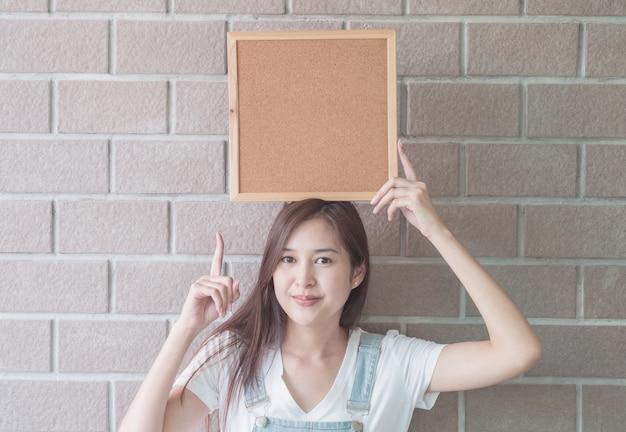 Mulher asiática com placa de cortiça na mão