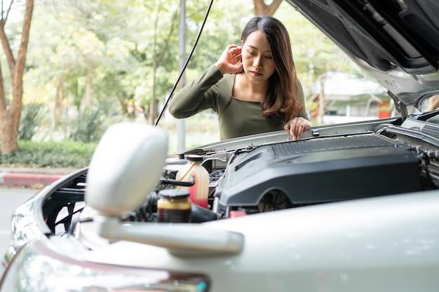 Mulher asiática com raiva e usando um telefone celular, pedindo ajuda após uma quebra de carro na rua. conceito de problema ou acidente no motor do veículo e ajuda de emergência de um mecânico profissional
