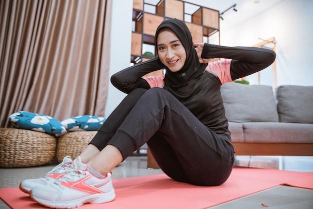 Mulher asiática com roupa de ginástica hijab sorri enquanto se senta em uma esteira no chão da casa