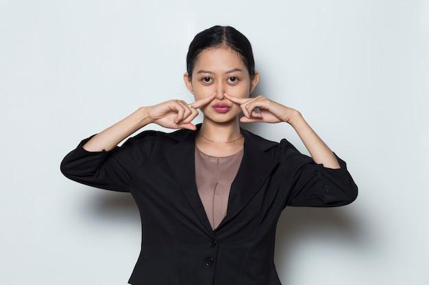 Mulher asiática com roupa formal segurando o nariz por causa de um cheiro ruim