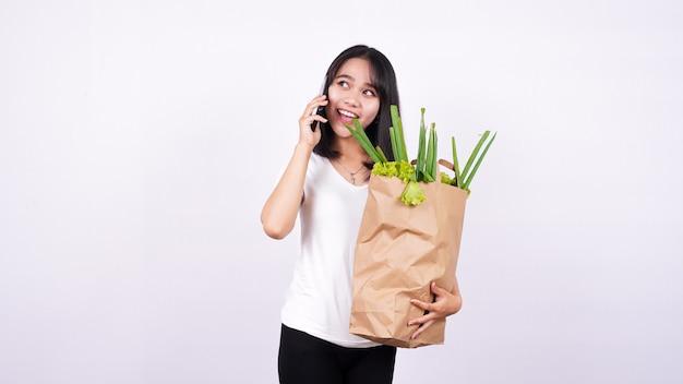 Mulher asiática com saco de papel de legumes frescos e falando ao telefone com uma superfície branca isolada
