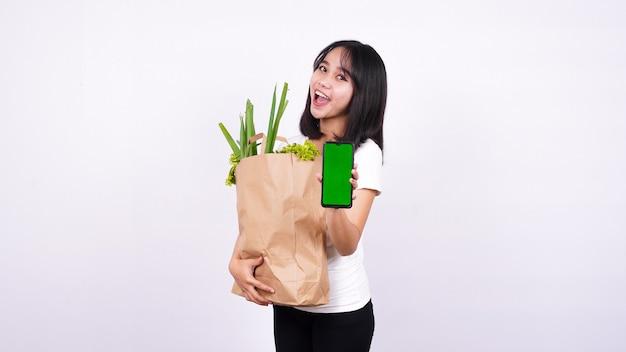 Mulher asiática com saco de papel de vegetais frescos e segurando um telefone de tela verde com superfície branca isolada