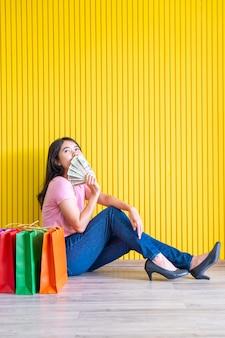 Mulher asiática com sacolas de compras cobrindo a boca com bilhetes