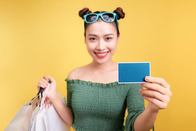Mulher asiática com sacolas de compras e um cartão de crédito em fundo amarelo