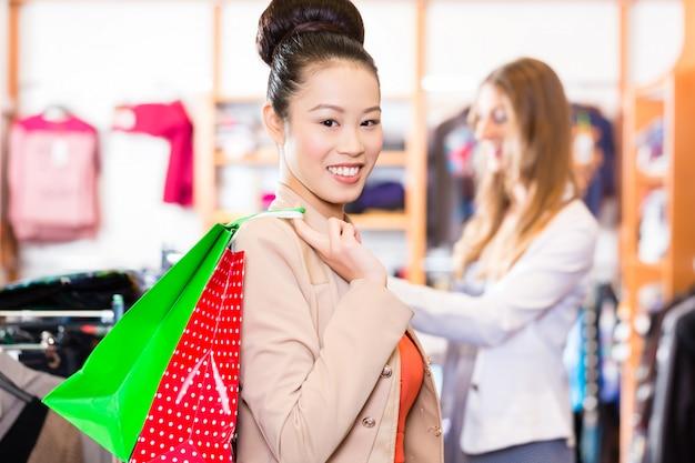 Mulher asiática com sacos de compras na loja