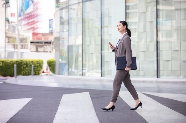 Mulher asiática com smartphone andando na rua desfocada