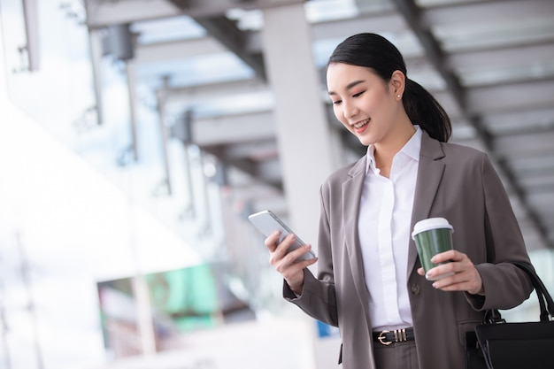 Mulher asiática com smartphone em pé contra o edifício rua turva. foto de negócios de moda de uma linda garota em uma suíte casual com telefone e xícara de café