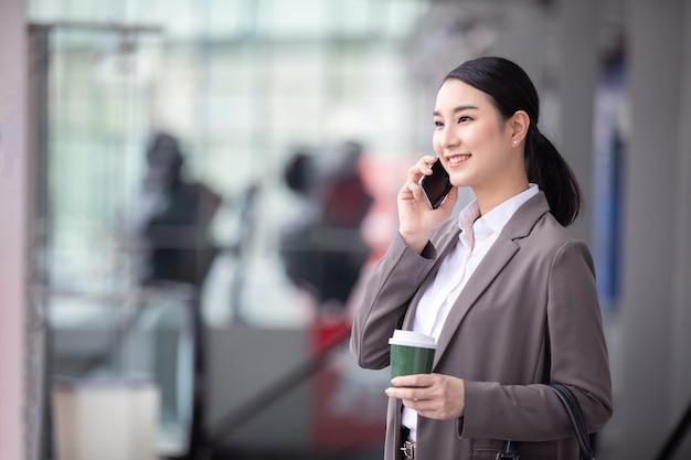 Mulher asiática com smartphone em pé contra um prédio de rua borrada