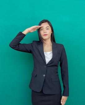 Mulher asiática com suíte de negócios recebe ação de ordem de comando na parede verde (incluir caminho)