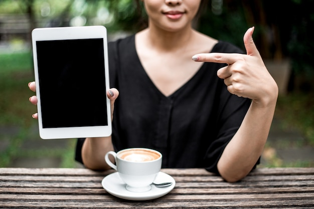 Mulher asiática com tablet e café.