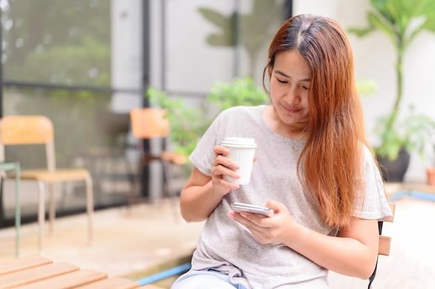 Mulher asiática com telefone celular e bebendo café sozinha. relaxe e recreação no jardim botânico nas férias.