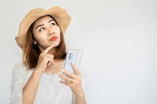 Mulher asiática com telefone inteligente sonhando, pensando em algo