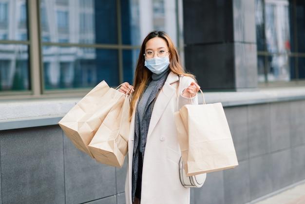 Mulher asiática com um casaco, óculos e uma máscara médica fica na rua, segurando um pacote nas mãos.