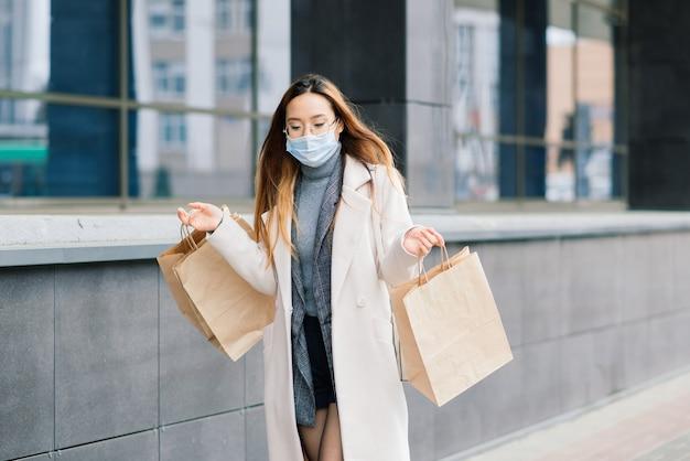 Mulher asiática com um casaco, óculos e uma máscara médica fica na rua