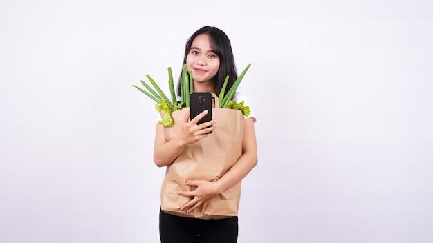 Mulher asiática com um saco de papel de legumes frescos e segurando um telefone com uma superfície branca isolada