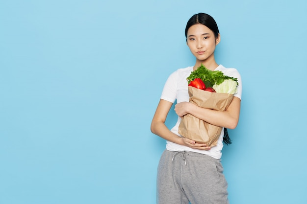Mulher asiática com um saco de vegerables