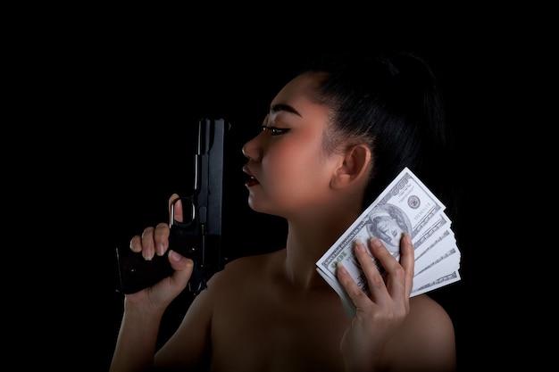 Mulher asiática com uma mão segurando uma arma e uma nota de dinheiro 100 dsd em fundo preto