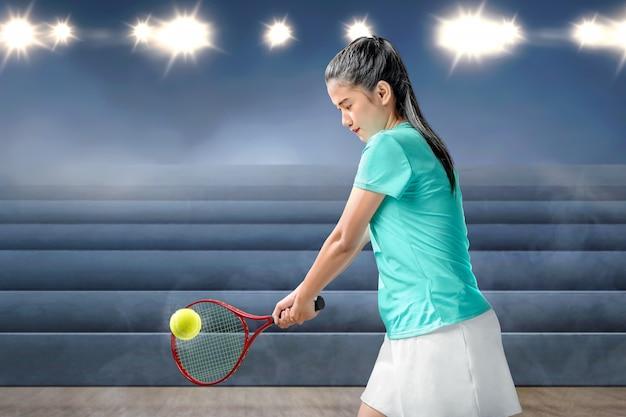 Mulher asiática com uma raquete de tênis nas mãos dela bate a bola