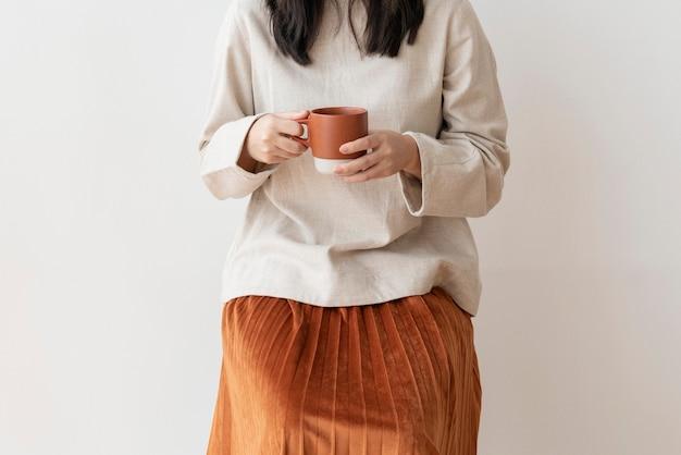 Mulher asiática com uma xícara de café na mão