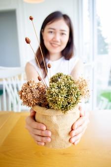 Mulher asiática com vaso de flores