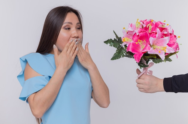 Mulher asiática com vestido azul parecendo feliz e surpresa cobrindo a boca com as mãos enquanto recebe um buquê de flores