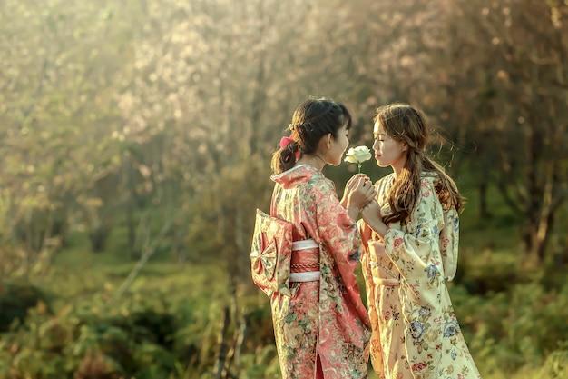 Mulher asiática com vestido camaleão tradicional no jardim sakura, tailândia