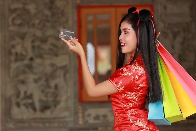 Mulher asiática com vestido chinês vermelho tradicional cheongsam qipao com gesto de mostrar o cartão de crédito e segurar sacolas de compras
