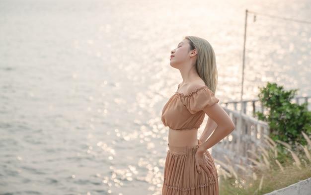 Mulher asiática com vestido posando na praia, momento do sol dourado do mar.