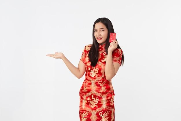 Mulher asiática com vestido qipao oriental e cartão de crédito vermelho na mão na superfície do estúdio cinza claro