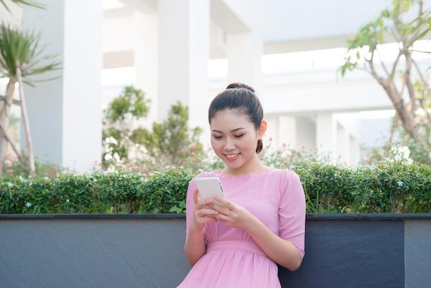Mulher asiática com vestido tradicional enviando mensagens de texto em um smartphone