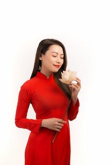 Mulher asiática com vestido tradicional vietnamita ao dai segurando uma flor de lótus como enfeite