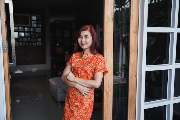 Mulher asiática com vestido vermelho com sorriso em pé