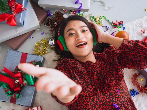 Mulher asiática, comemorando o ano novo e o natal no chão com caixa de presente