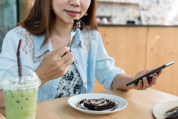 Mulher asiática comendo bolo de brownie enquanto usa o smartphone.