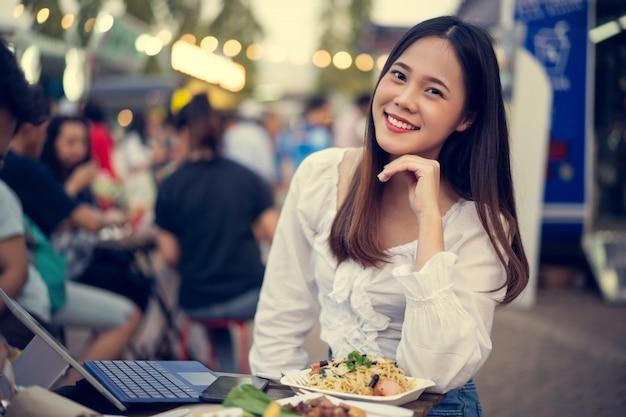Mulher asiática comendo comida de rua e trabalhando em sua empresa