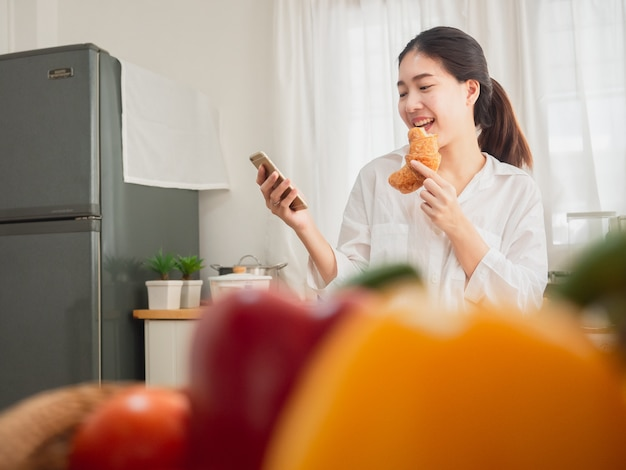 Mulher asiática comendo pão enquanto estiver usando o telefone inteligente na cozinha