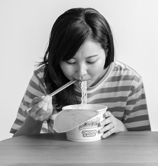 Mulher asiática comendo um macarrão instantâneo