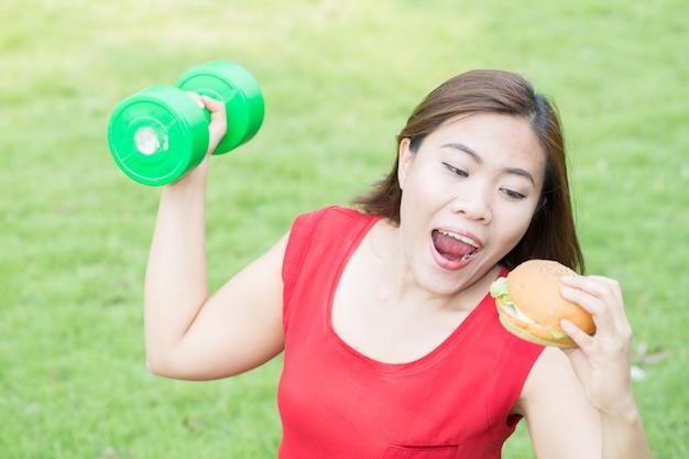Mulher asiática, comer hambúrguer com levantamento de peso