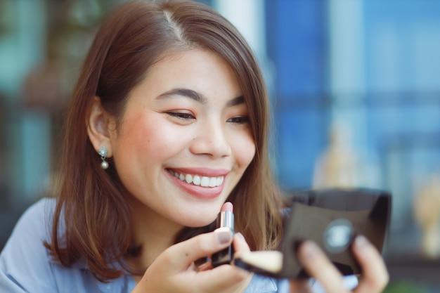 Mulher asiática compõem o rosto com batom no café